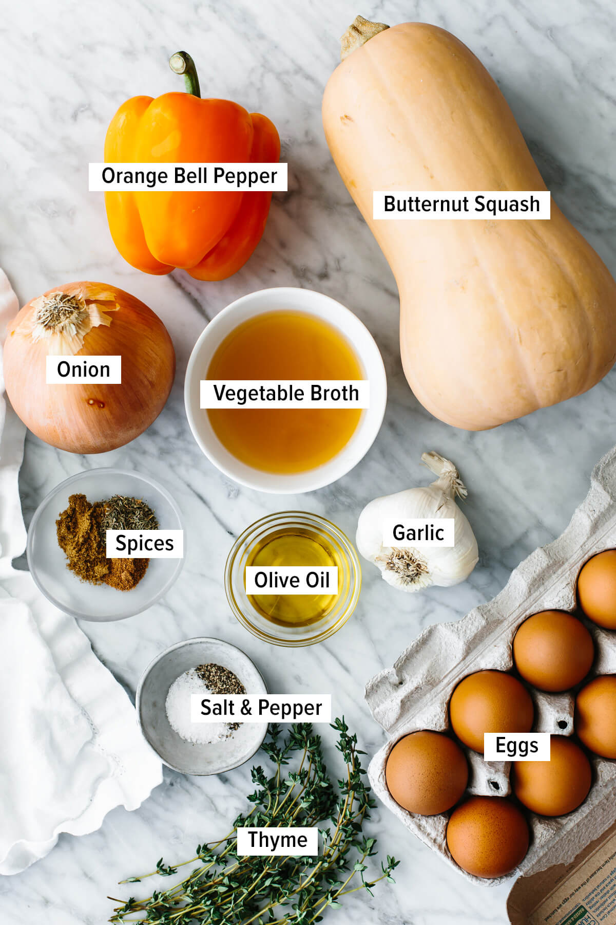 Ingredients for an orange shakshuka laid out on a table.