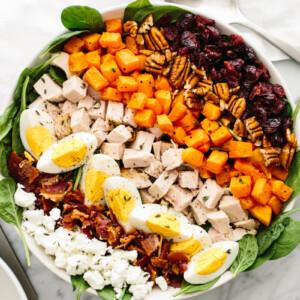 A large bowl with turkey cobb salad next to a vinaigrette bowl.