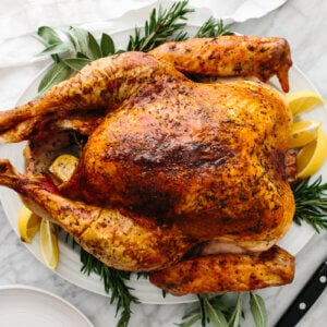 Thanksgiving turkey on a plate with sage and lemons.