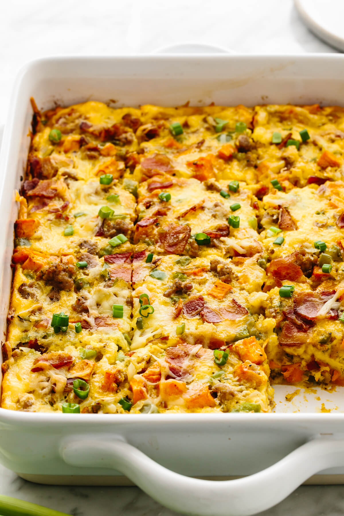 Breakfast casserole in a pan, sliced into pieces.
