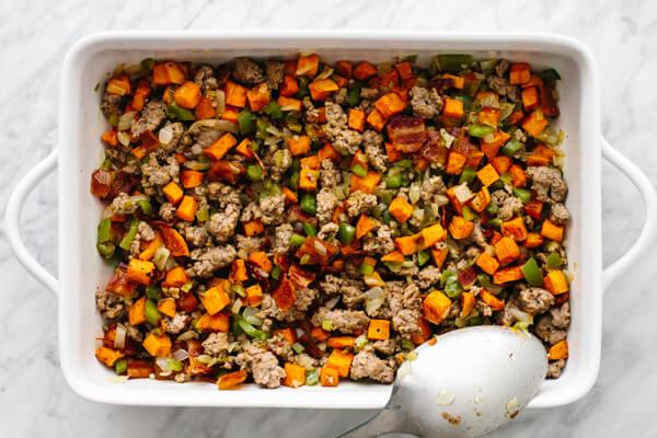 Stir ingredients in a pan for a loaded breakfast casserole.