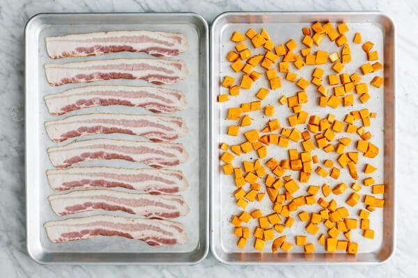 Bacon and sweet potatoes on baking sheets.