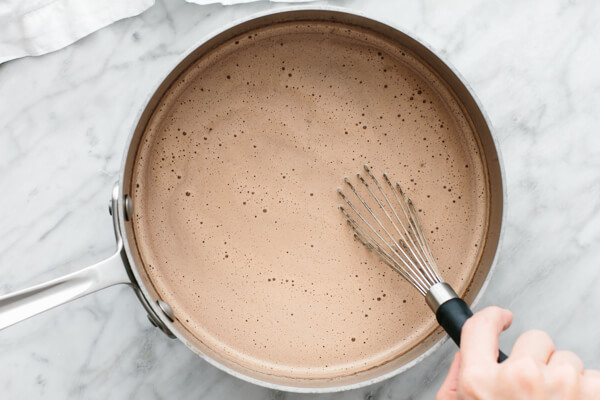 Whisking Nutella hot chocolate in a pot.