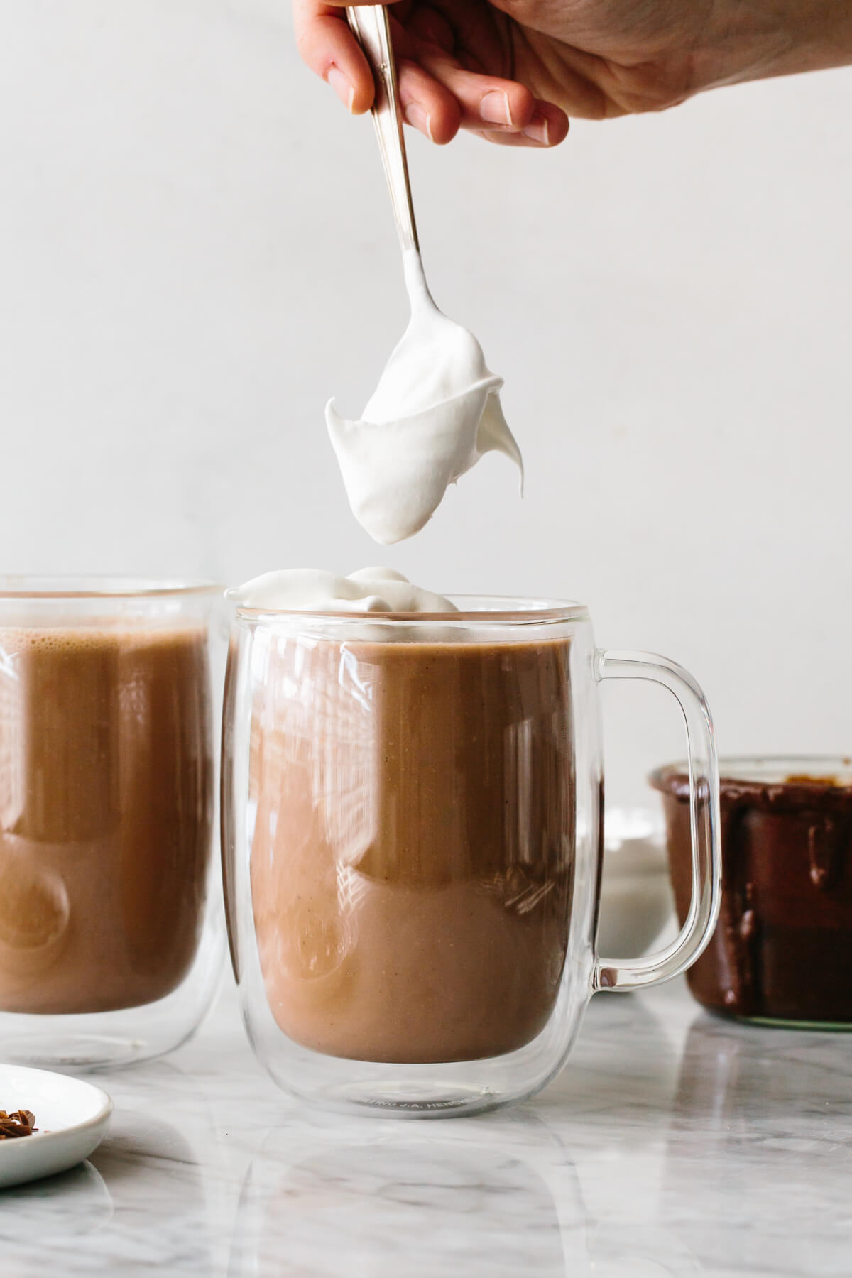 Adding whipped cream on top of Nutella hot chocolate.