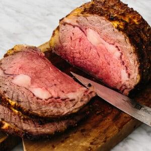 Prime rib on a cutting board sliced up.