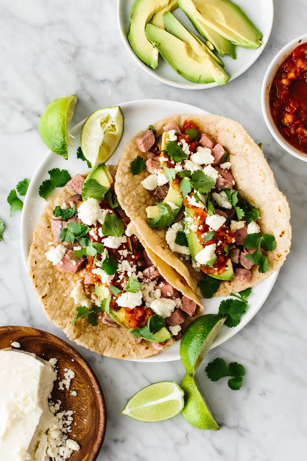 Two prime rib tacos on a plate.
