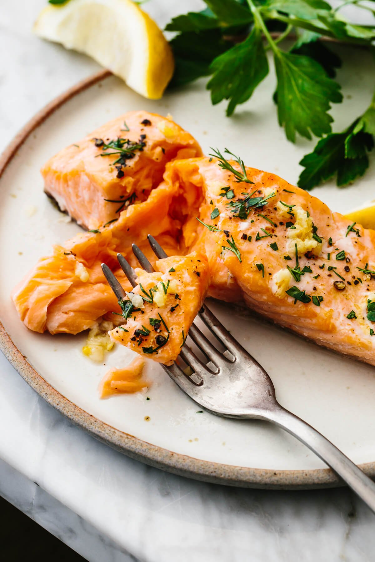 Baked salmon on a plate with a fork and parsley.