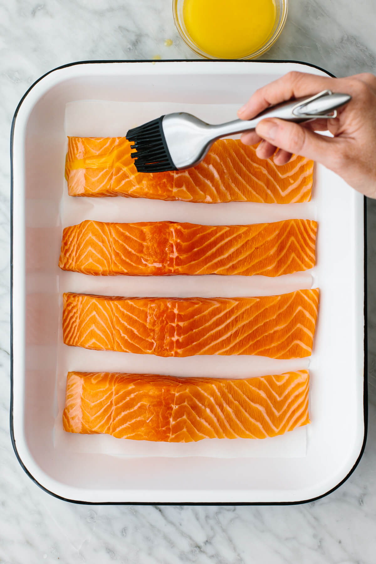 Brushing butter on baked salmon in a pan.