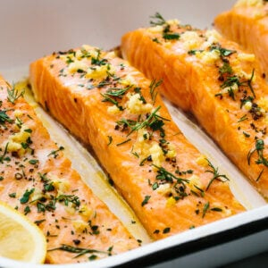 Baked salmon fillets in a pan with garlic and herbs.