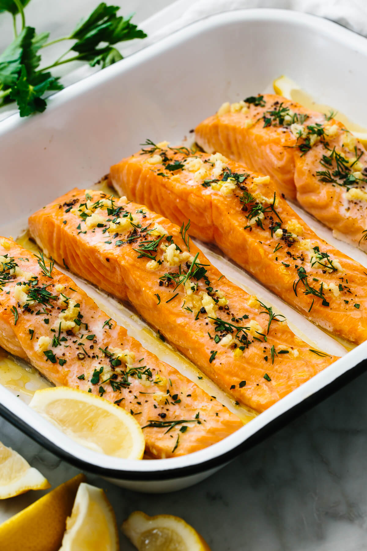 Baked salmon in a pan next to lemon wedges.