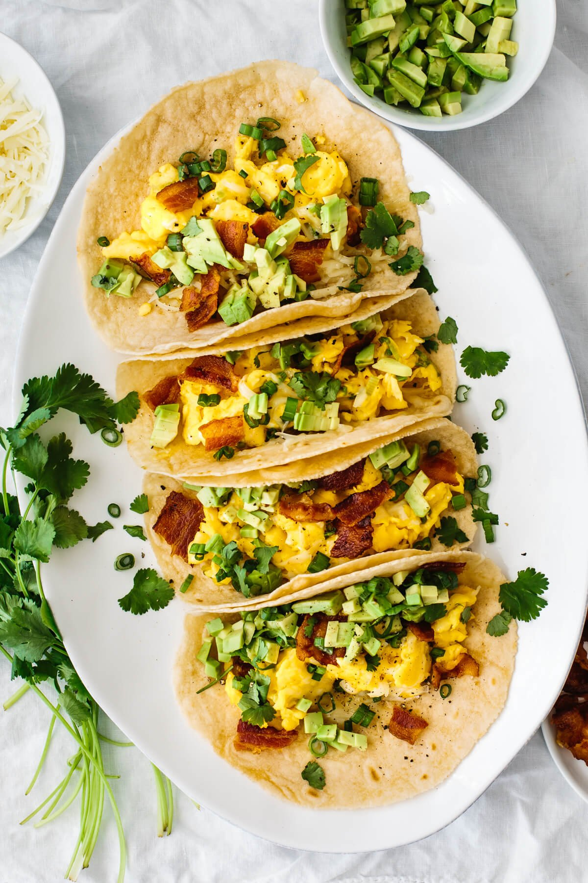 Breakfast tacos on a plate next to cilantro and avocado.