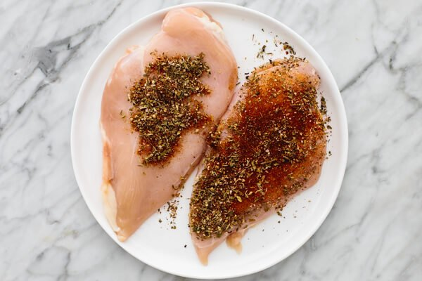 Two chicken breasts coated in spices.