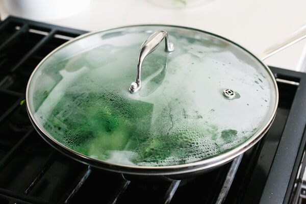 Covering a pan of garlic sauteed spinach for steaming.
