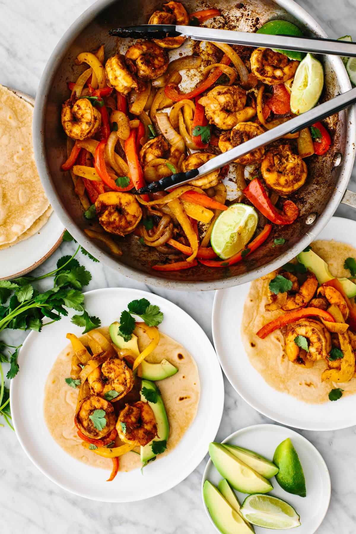 A pan of shrimp fajitas next to tacos on plates.