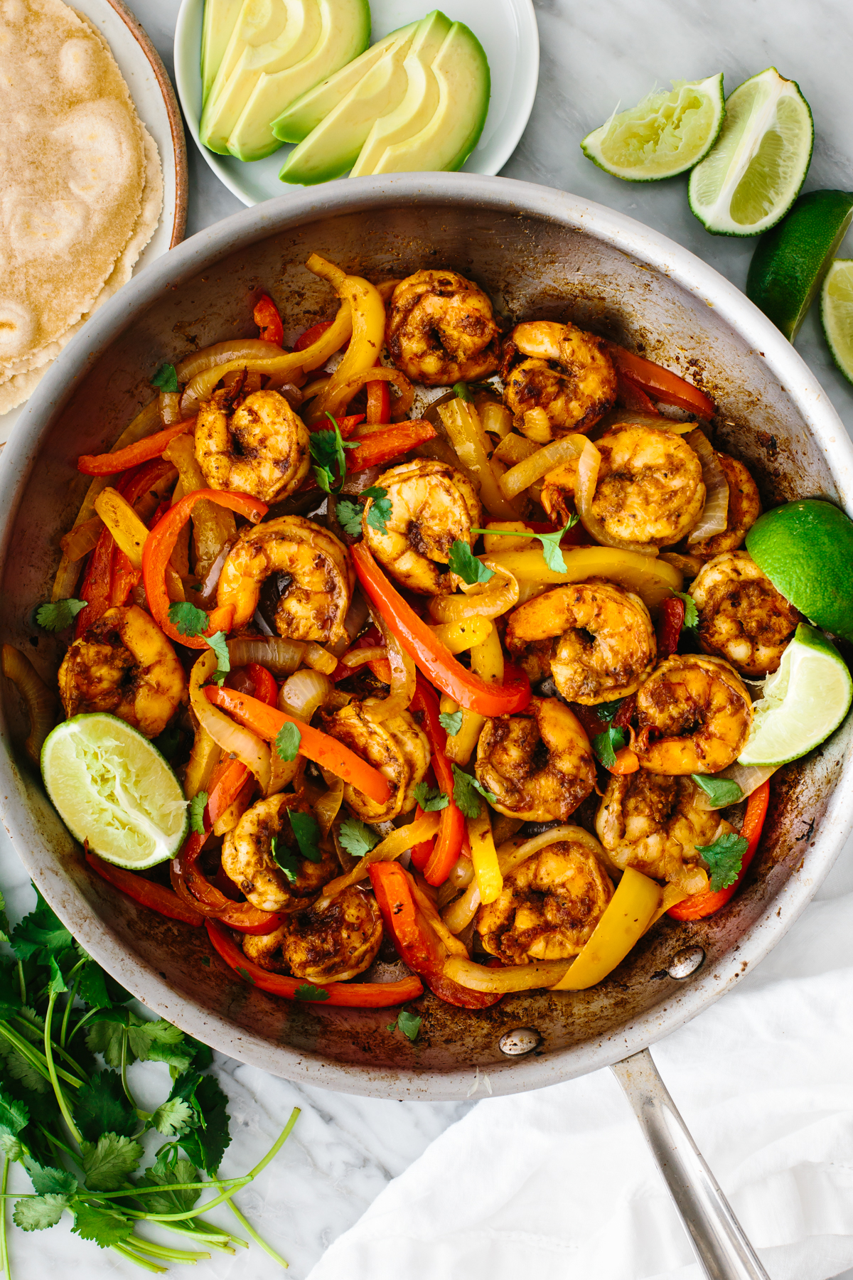 Shrimp fajitas in a pan with avocado slices and lime wedges.