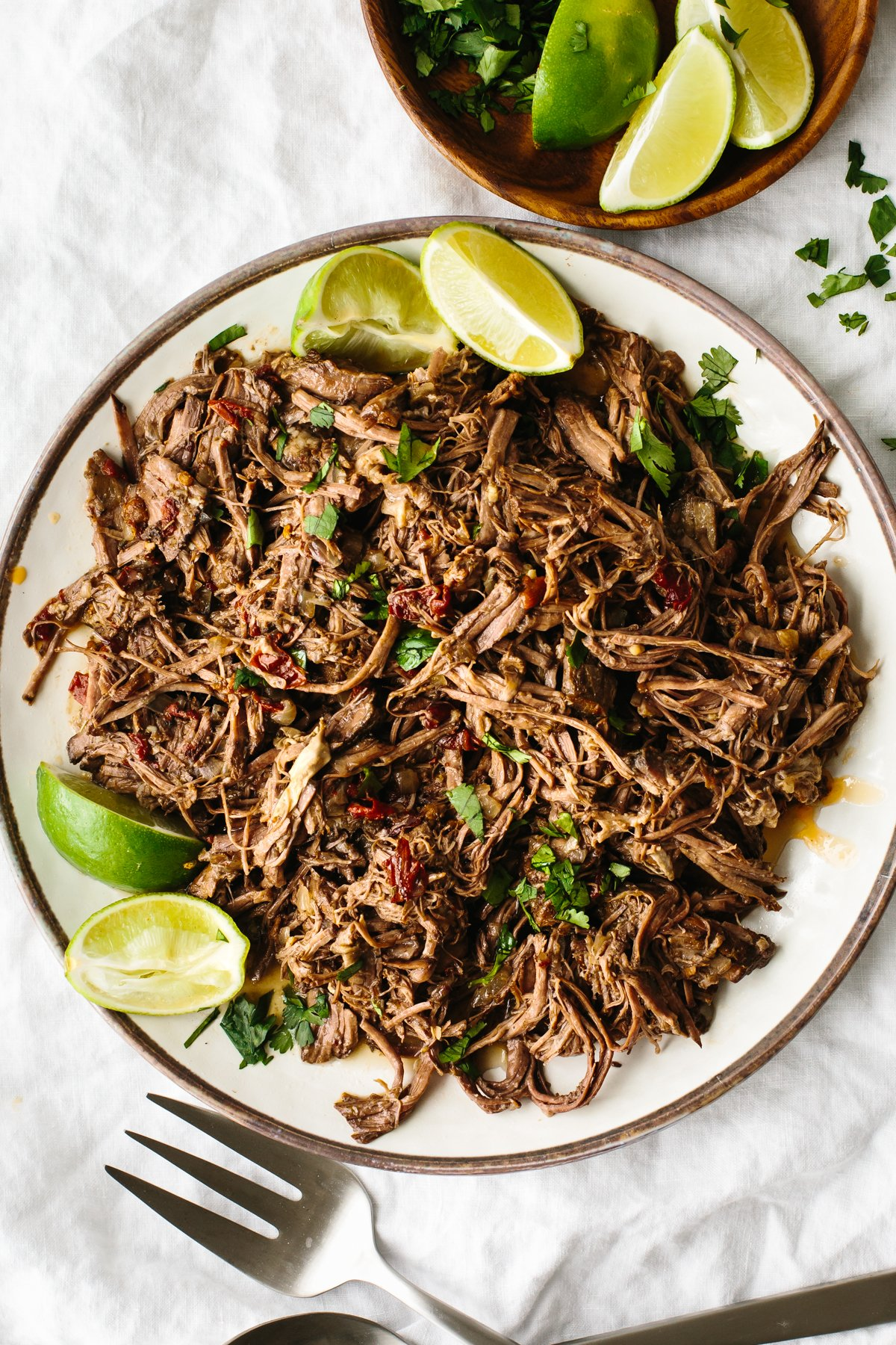 Beef barbacoa on a plate with lime wedges.