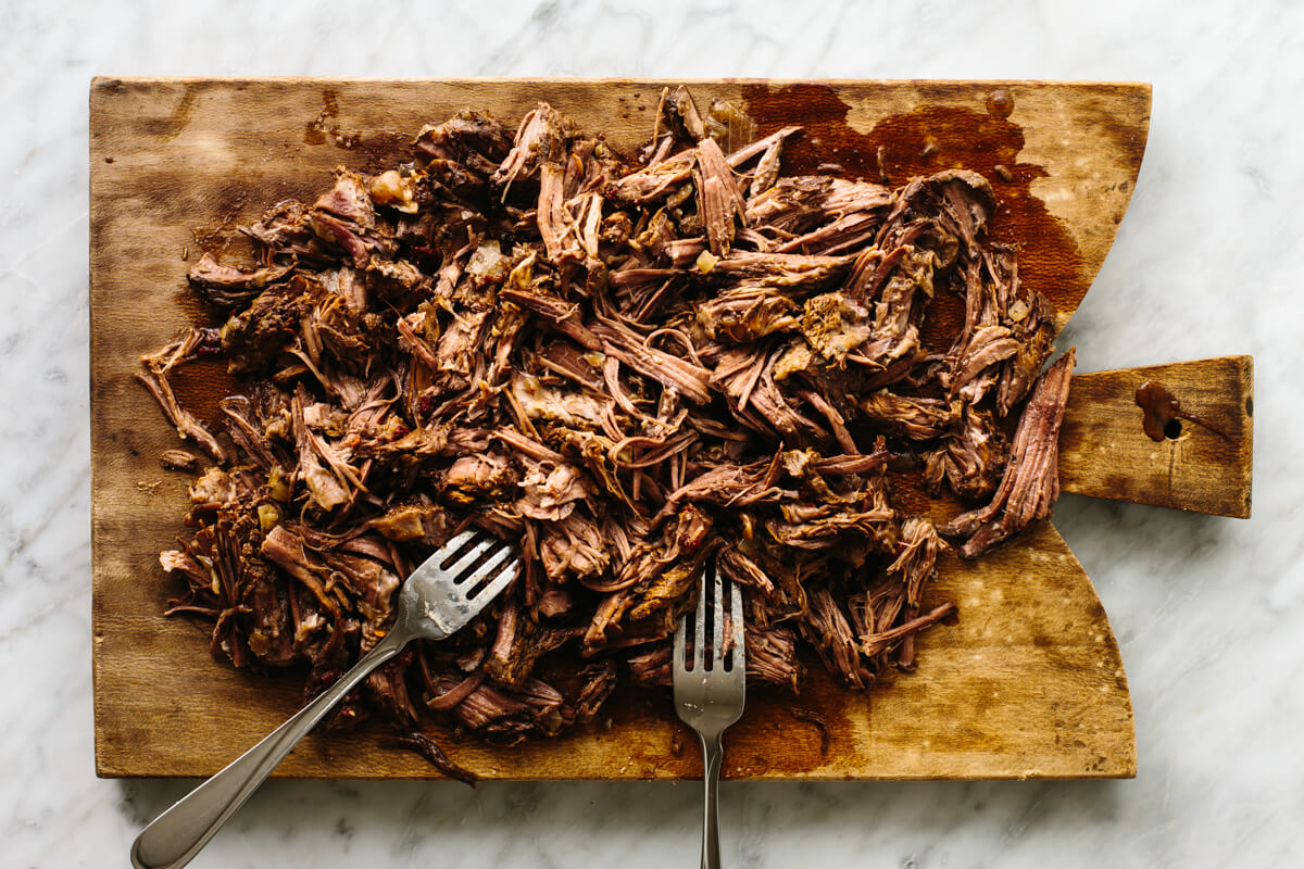 Shredded beef barbacoa on a wooden board with forks.