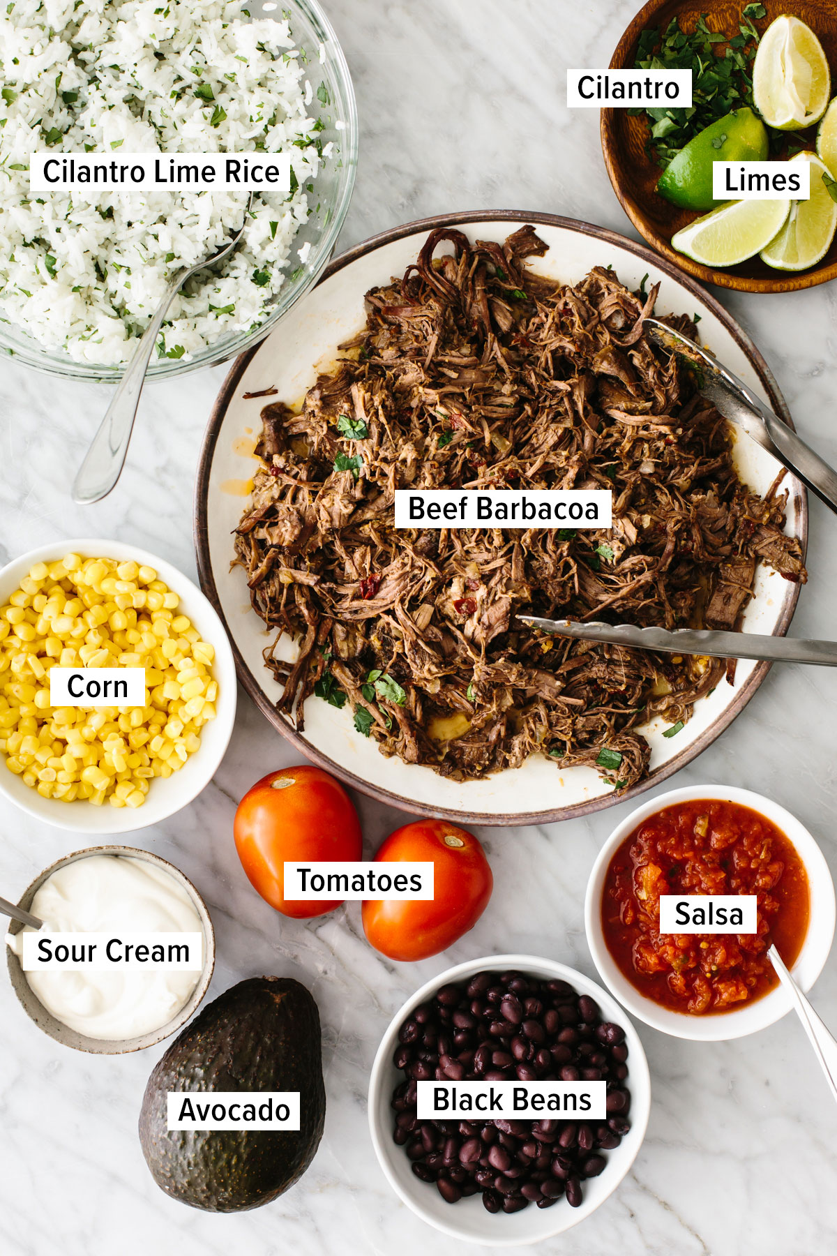 Ingredients for a barbacoa burrito bowl on a table.
