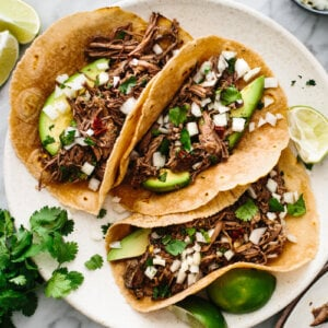 Barbacoa tacos next to cilantro, lime, and tortillas.