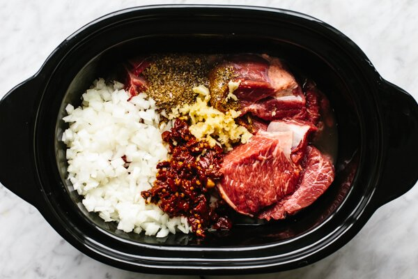 Adding beef barbacoa ingredients into the slow cooker.