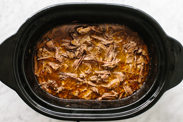 Mixing beef barbacoa in a slow cooker.