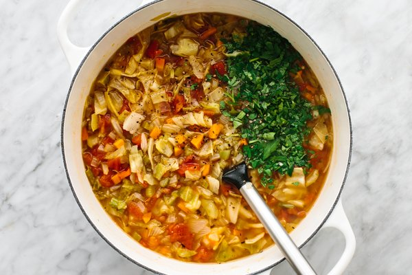 Stirring ingredients in a large pot for cabbage soup.
