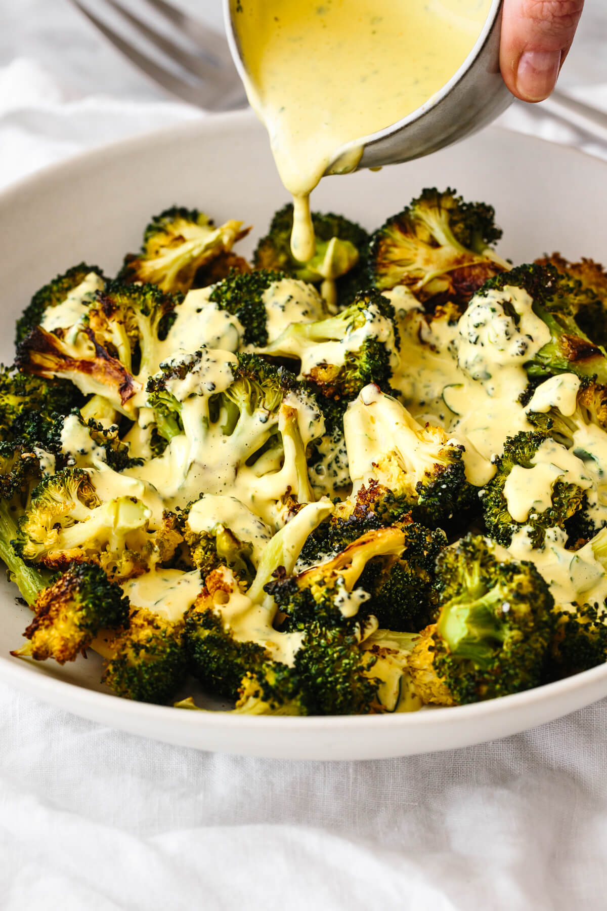 Pouring hollandaise sauce over roasted broccoli.