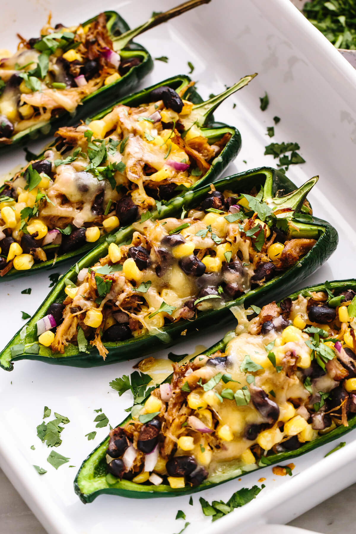 A baking dish with carnitas stuffed poblano peppers.