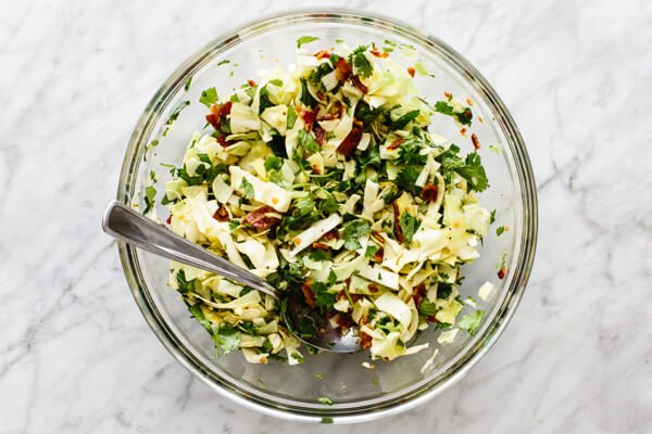 Tossing together cilantro lime bacon coleslaw in a bowl.