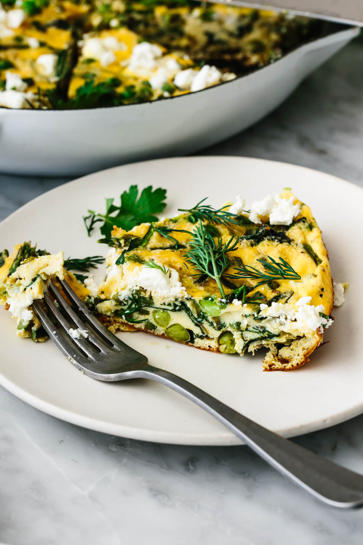 A slice of spring vegetable frittata on a plate