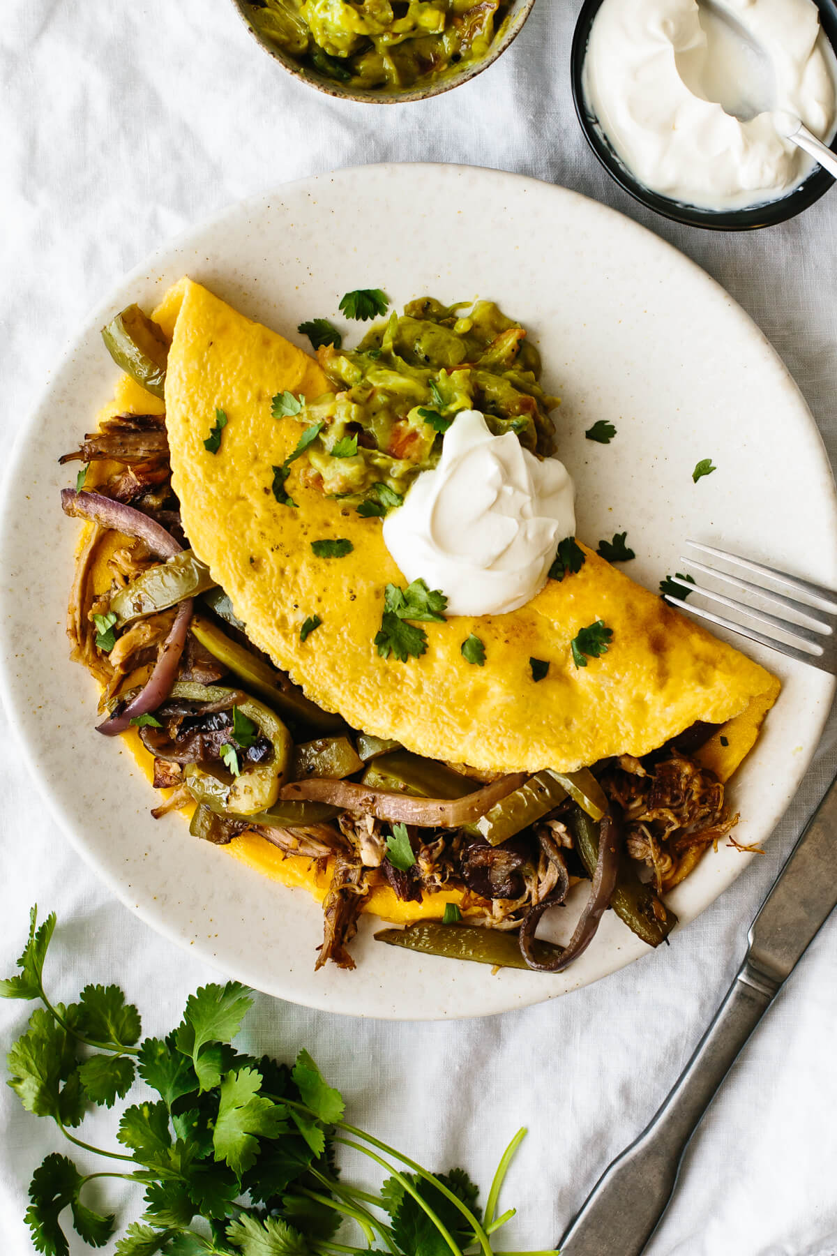 Carnitas omelette with fajita veggies on a plate.