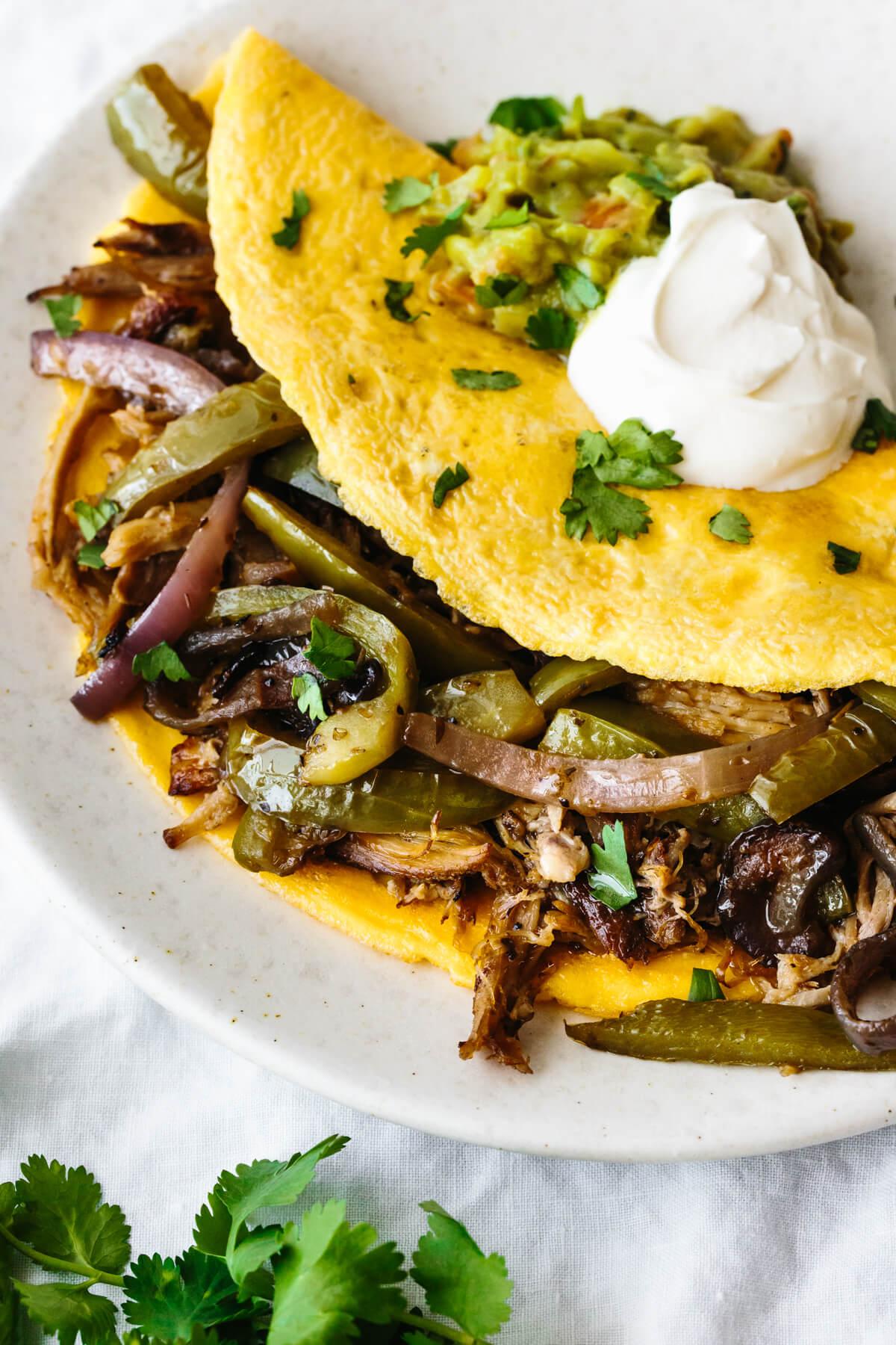 A plate of carnitas omelette with fajita veggies and sour cream.