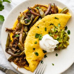 Omelette with carnitas and fajita veggies next to cilantro