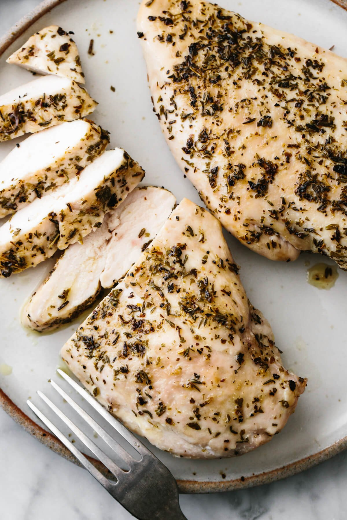 Herb baked chicken breast sliced into pieces on a plate.