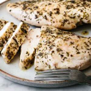 A plate of herb baked chicken breast slices.