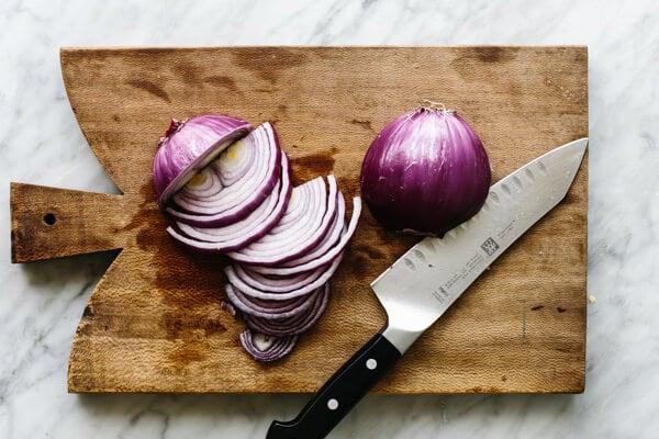 Slicing onions on a cutting board for fajita veggies.