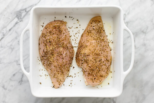 Adding seasoning onto herb baked chicken breasts in a baking dish.