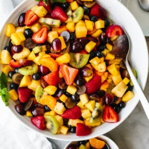 A large serving bowl of fruit salad on a table.