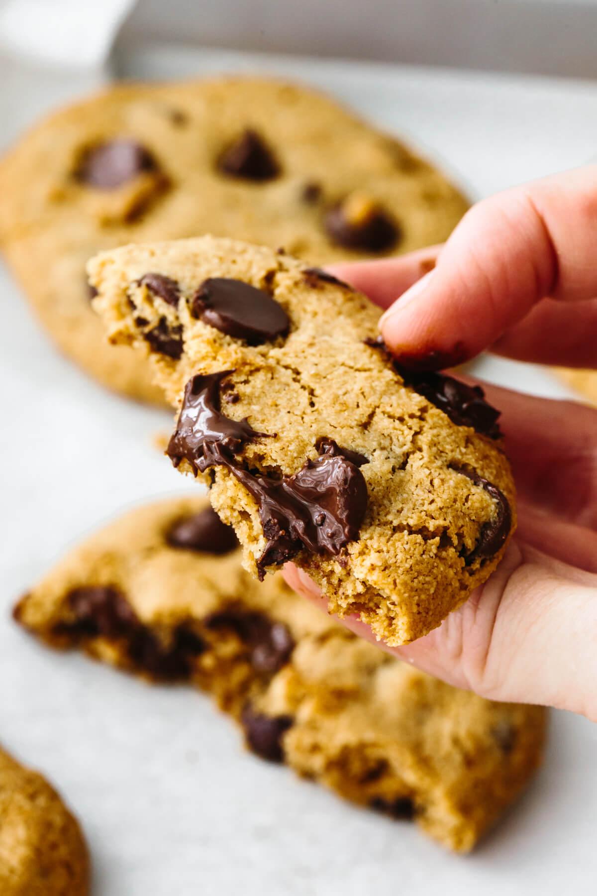 Holding a bitten gluten-free chocolate chip cookie