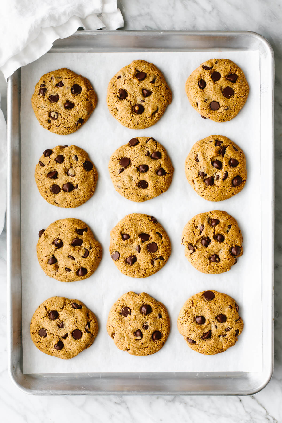 A metal sheet pan with gluten-free chocolate chip cookies lined up.