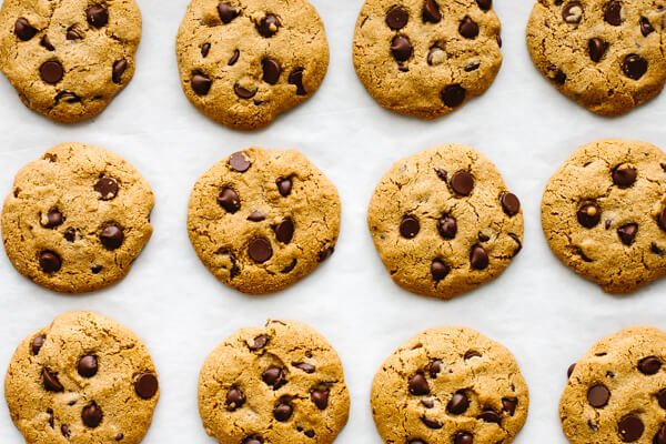 Gluten-free chocolate chip cookies lined up on a sheet pan.