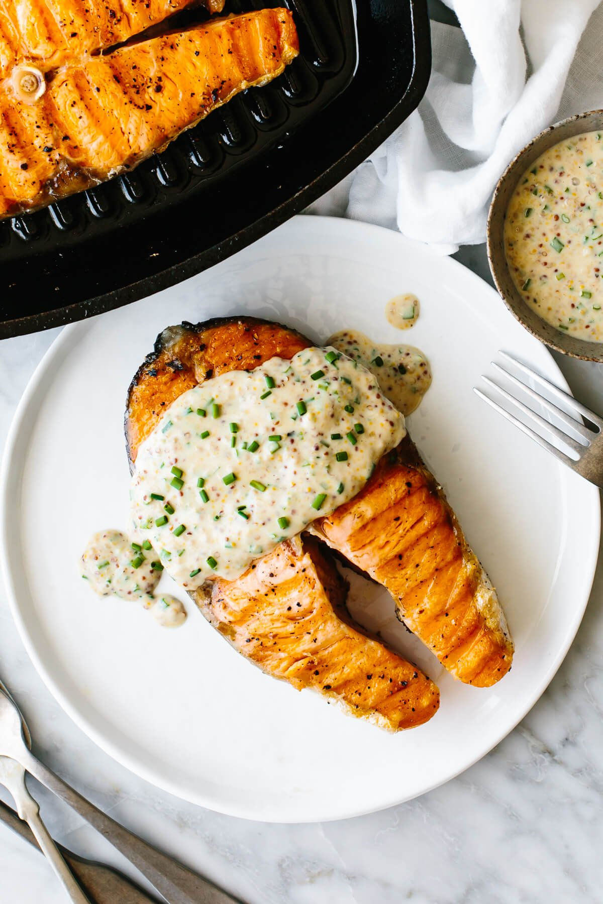 Grilled salmon steak on a plate next to a skillet