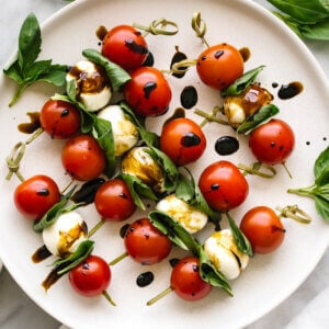 A plate of caprese skewers with basil leaves