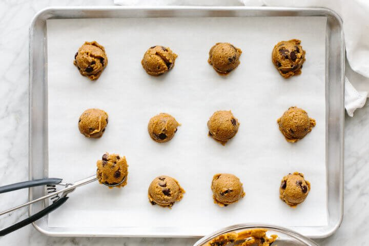Dolloping cookie dough onto a parchment lined baking sheet.