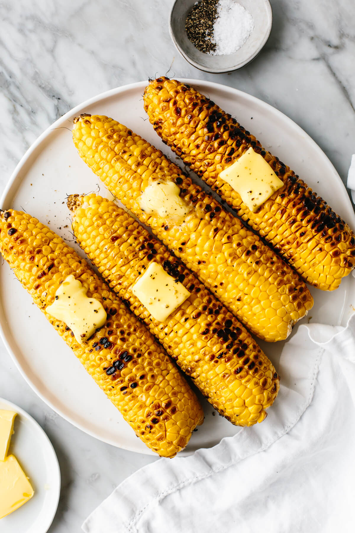 Grilled corns on the cobb on a white plate next to butter.