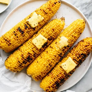 A plate of four grilled corn on the cobs