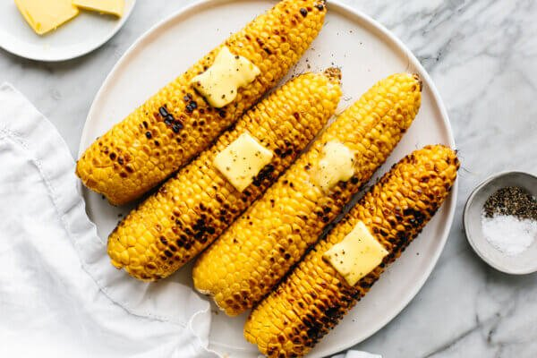 A circle plate with grilled corn on the cobs next to salt and pepper.