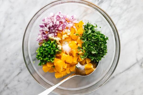 Mixing mandarin orange salsa ingredients in a bowl.