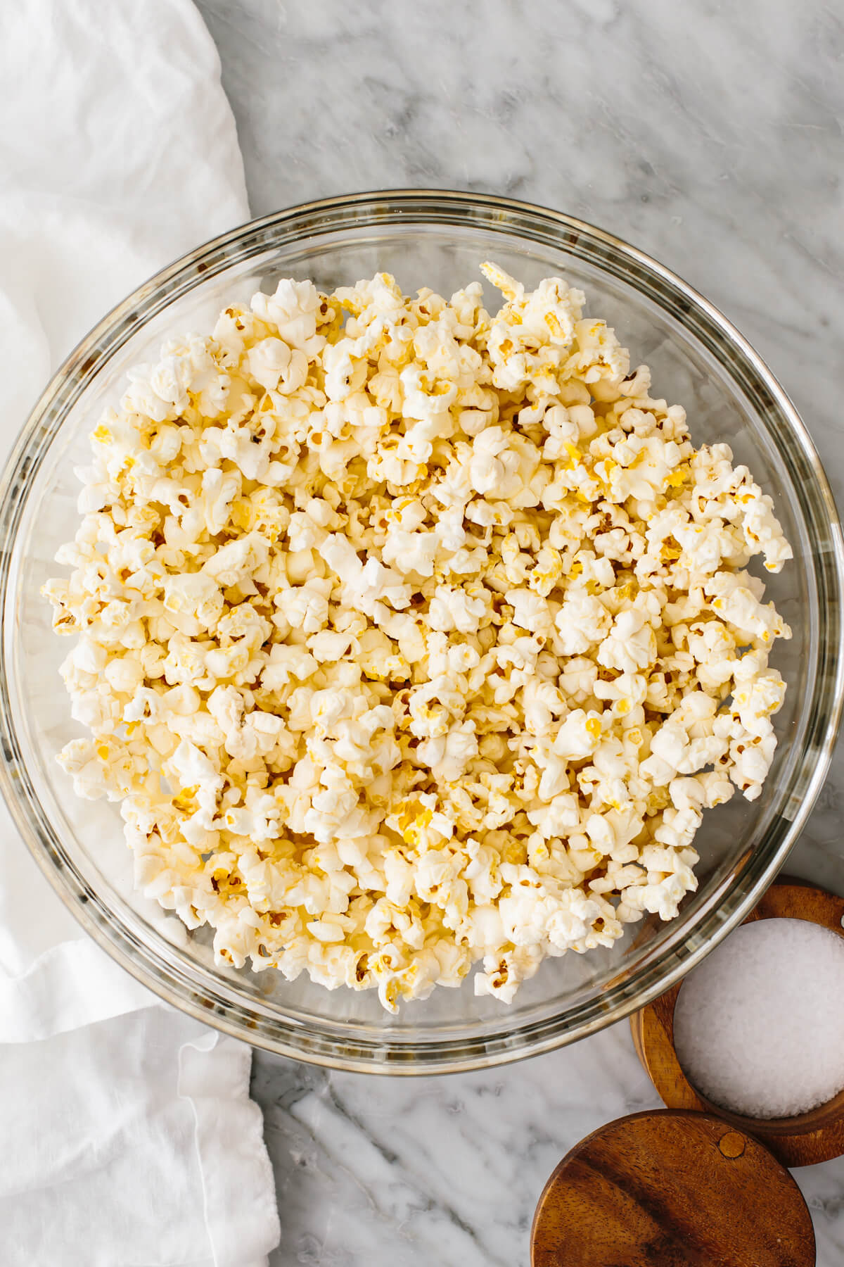 Microwave popcorn in a glass bowl on a table.