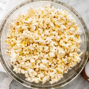 A big glass bowl of popcorn next to a napkin.